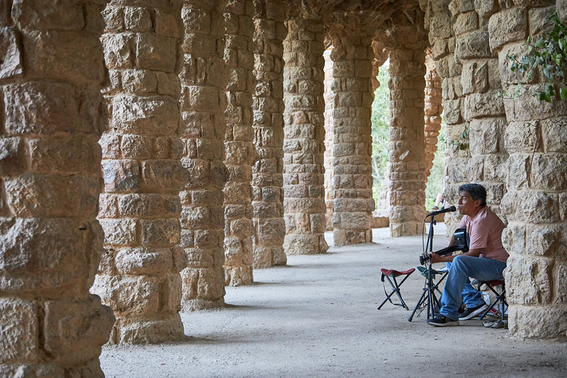 A busker beneath the arches of Park Guell
