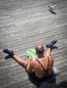 Man Feeding Seagulls while sunbathing, Barcelona