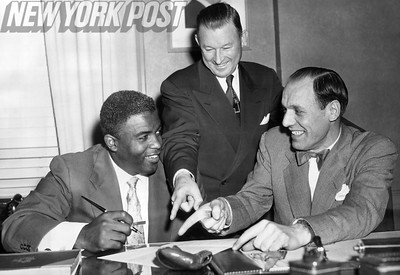 Jackie Robinson signs his 1952 Brooklyn Dodgers contract with Buzzie Bavasi and Chuck Dressen. 1952