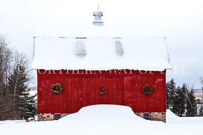 Snowy red barn all decked out for Christmas