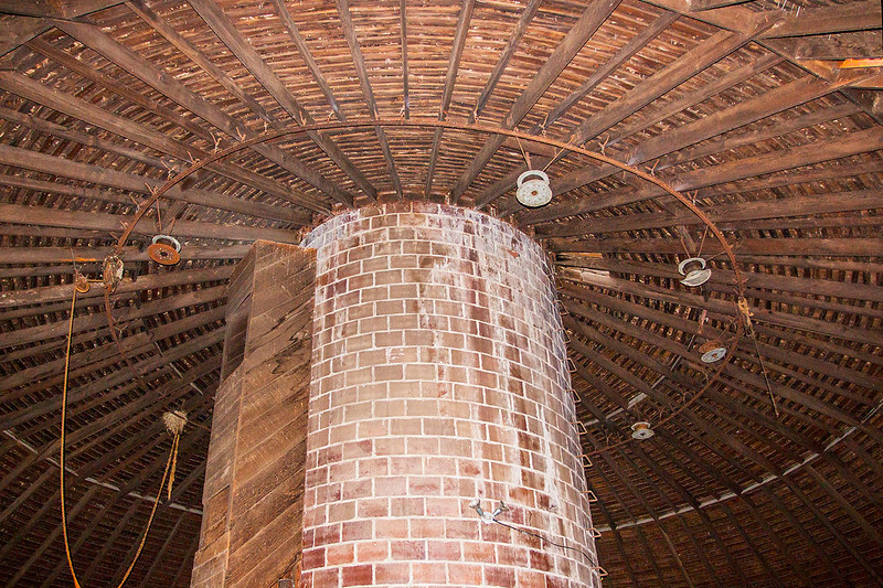 Clay tile silo in center of round barn with roof support.
