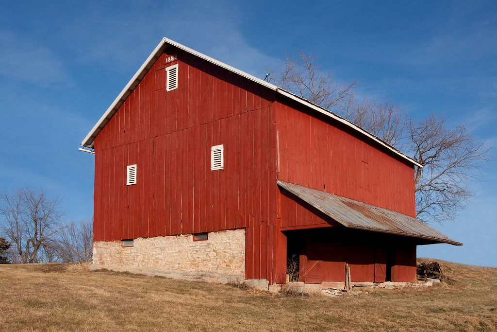 The Pennsylvania-style barn was built in 1885. A typical bank barn with entrance ramp gives access to the second floor on the North side. The lower level with animal stalls has a protecting overhang and doors facing the South. Stone for the foundation was quarried locally as well as the lumber coming from the barn site. Hand hewn beams with mortise and tenon construction and wooden pegs.