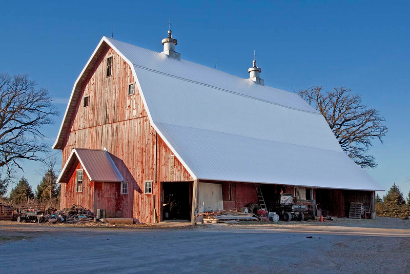 The barn was built in 1922 on land that has been in the same family since 1914. Third generation now living on the farm.This barn has the Dutch style Gambel roof with over hanging roof line for weather protection. The framing for the barn was built with native oak from the barn site. Beams are pegged mortise and tenons. The barn has two ornate metal cupola ventilators. The barn with its lower roofline has withstood major wind storms in 1998 and 2008. The barn was used as 1/2 dairy barn and 1/2 horse barn.