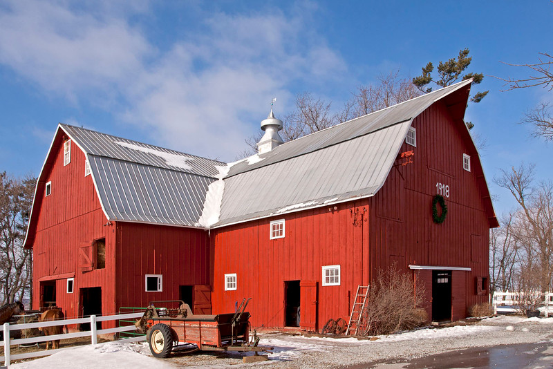 The barn was built in 1918 and still is original inside and out. It has a Dutch Gambrel roof. The roof has been replaced with metal, but it is the same metal that would have been used when the barn was built.The barn is unique because it has 3 gable ends. Two of the gable ends have hay doors with original hay track and carrier to haymow. There are three grain bins on the upper floor that have the original track and carrier.The haymow has a haybay (opening) to the hay racks on ground floor below. The horse and cow stalls are original. The barn is still in use as a horse barn.