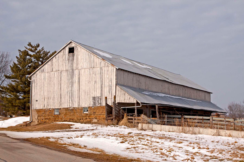 The Rinderstall (cow) barn in West Amana. Limestone and sandstone foundation. One side is a bank barn with <br /> two double doors to upper level. The opposite side has a protecting overhang the lengh of the  barn for the lower level.