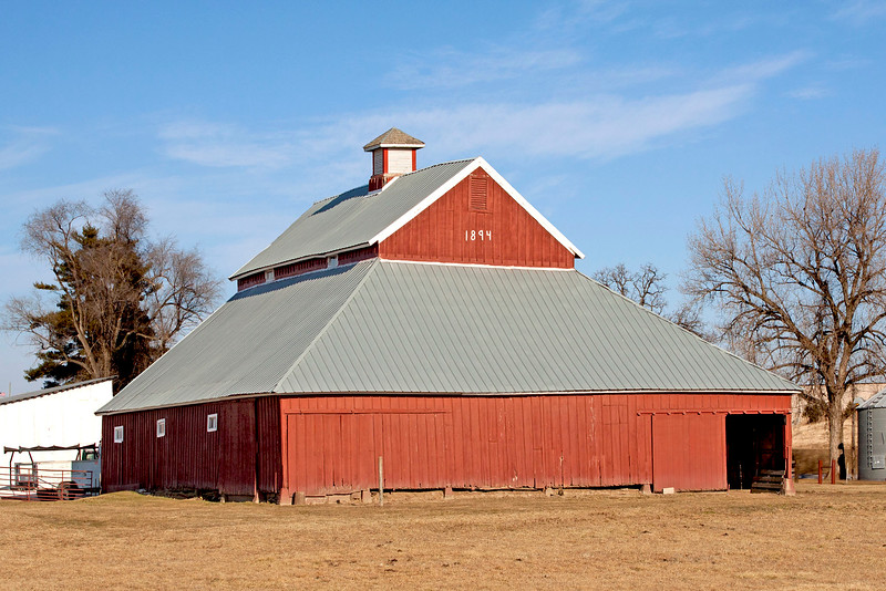 Built in 1894, this barn has a unique center haymow which goes from ground level to the peak of the roof. It held some 10,000 bales of hay. The lower hip roof section that wraps around the center haymow was for the cattle. In 1997, a strong wind moved the barn a foot off its foundation and caused it to lean sideways. With ropes, pulleys and leverages, a crew of Amish men movedit back onto the foundation and straightened it.