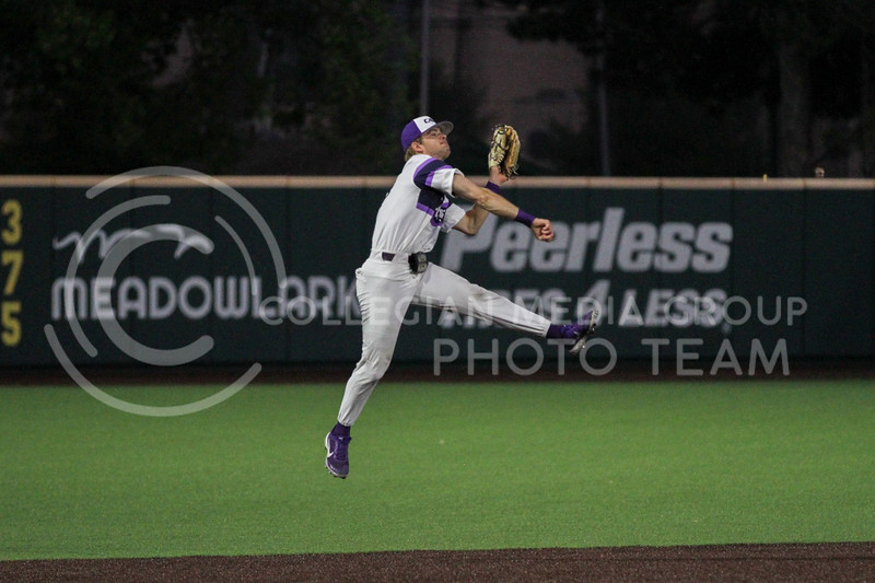 Freshman Nick Goodwin leaps in the air to throw the ball to a teammate during the April 27, 2021 game against Missouri at Tointon Family Stadium. (Sophie Osborn | Collegian Media Group)