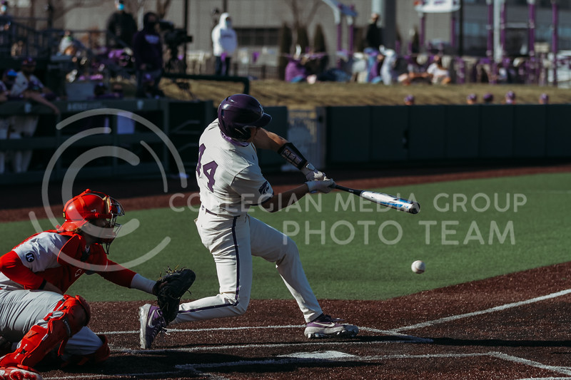 Junior catcher Dylan Caplinger hits the ball during the game on March 20, 2021 against New Mexico at Tointon Family Stadium. ( Sophie Osborn   Collegian Media Group)