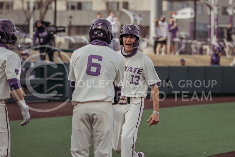Senior Caleb Littlejim celebrates with teammates after getting to home base during the teams season opener against Western Michigan on February 26th at Tointon Family Stadium. (Sophie Osborn | Collegian Media Group)