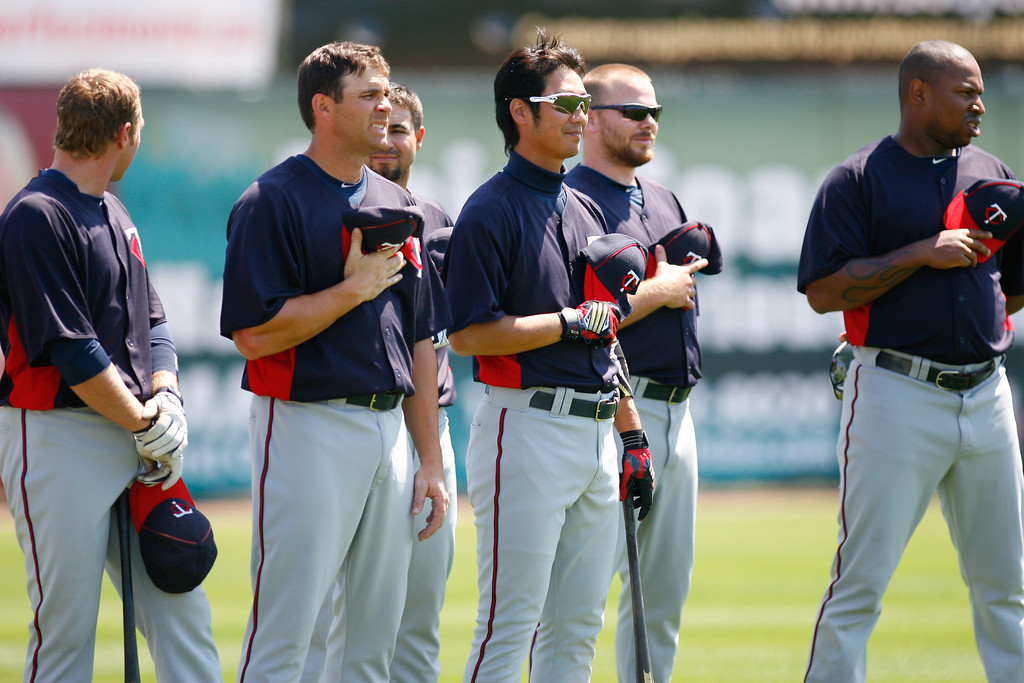 Minnesota Twins second baseman Tsuyoshi Nishioka (1) stand with teammates during the national anthem prior to a Grapefruit League Spring Training Game at the Florida Auto Exchange Stadium.