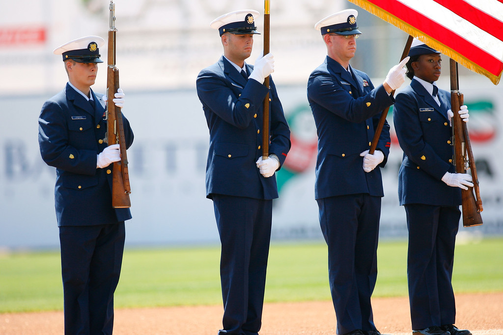 U.S. Coast Guard holds flag during the national anthem prior to a Grapefruit League Spring Training Game at the Florida Auto Exchange Stadium.