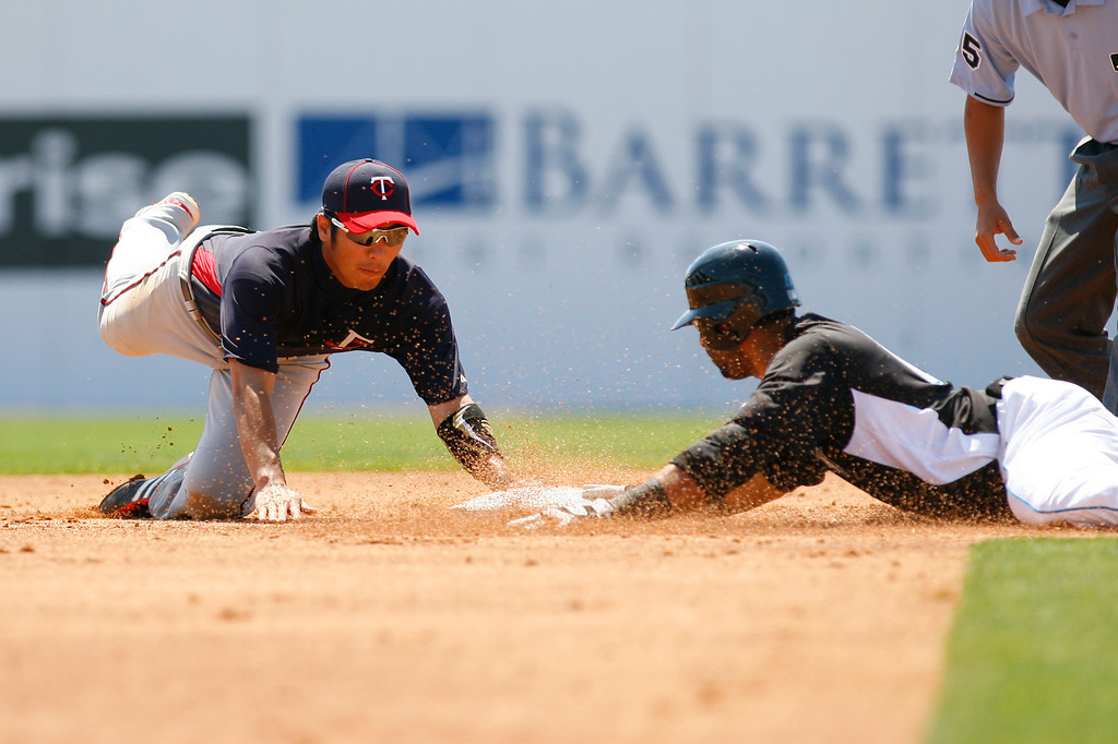 Minnesota Twins second baseman Tsuyoshi Nishioka (1) attempts to tag out Toronto Blue Jays third baseman Jose Bautista (19) at second base in the bottom of the first inning of a Grapefruit League Spring Training Game at the Florida Auto Exchange Stadium.