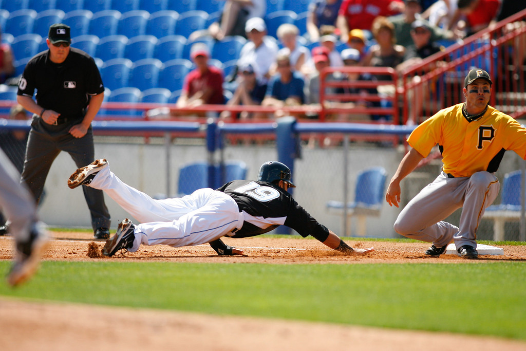 Toronto Blue Jays right fielder Jose Bautista (19) dives into first base during to avoid being picked off a Grapefruit League Spring Training Game at the Florida Auto Exchange Stadium.