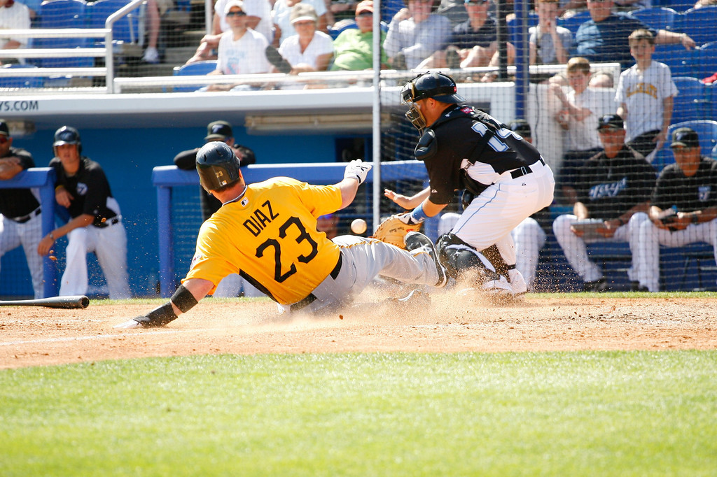 Pittsburgh Pirates OF Matt Diaz (23) slides into home scoring the go ahead run in the top of the sixth inning during a Grapefruit League Spring Training Game at the Florida Auto Exchange Stadium.