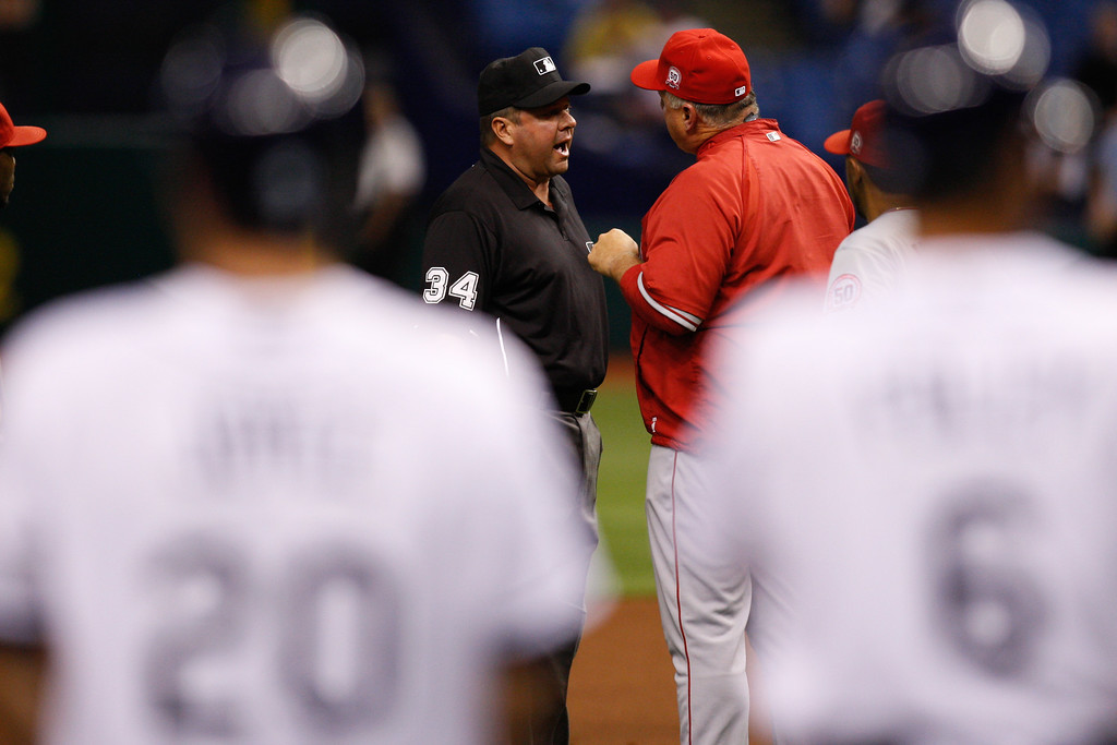 Los Angeles Angels manager Mike Scioscia (14) argues with umpire Sam Holbrook (34) over a play during the game at Tropicana Field.