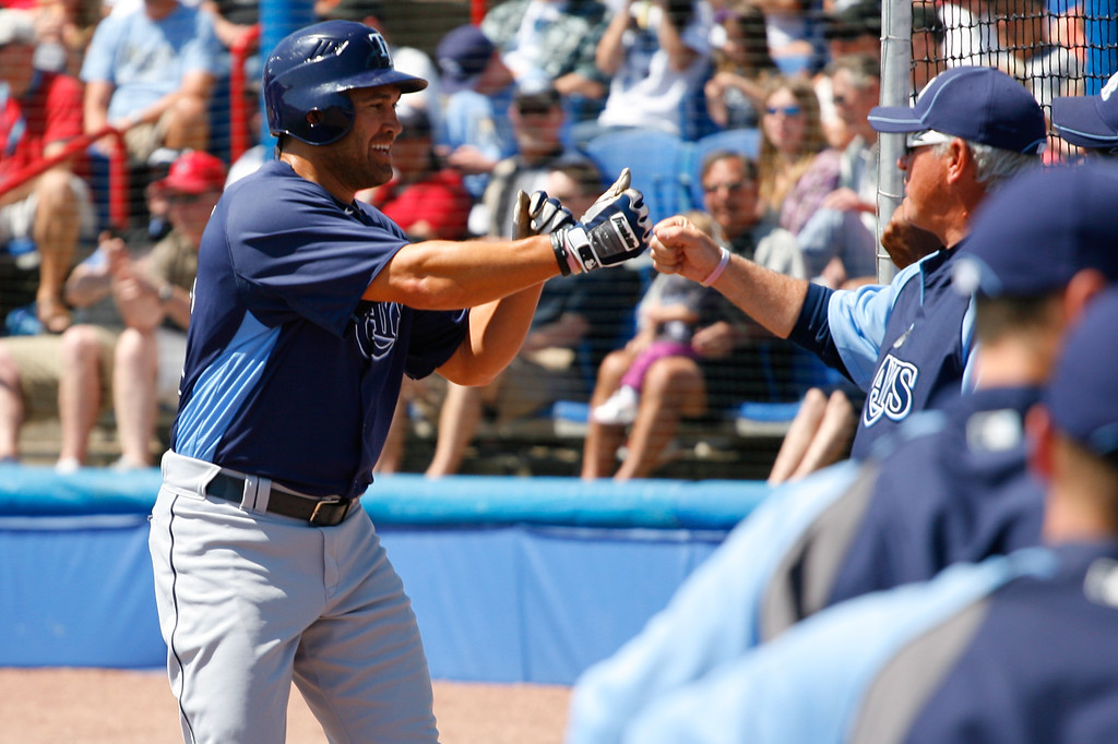 Tampa Bay Rays left fielder Johnny Damon (22) celebrates with Tampa Bay Rays manager Joe Maddon (70) after scoring a run during a Grapefruit League Spring Training Game at the Florida Auto Exchange Stadium.