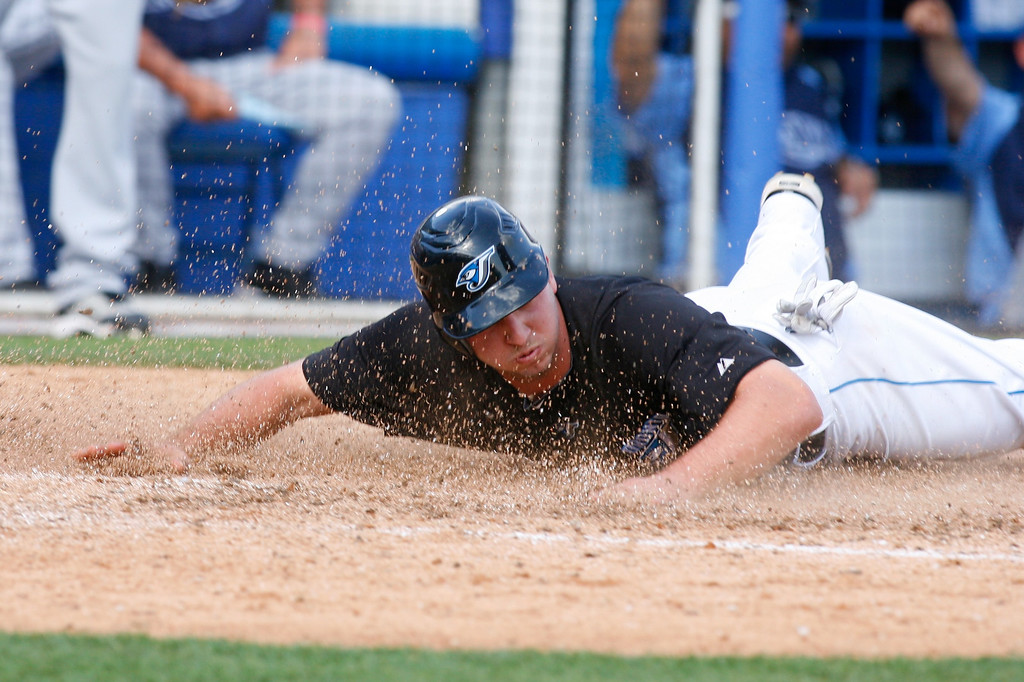 Toronto Blue Jays infielder David Cooper (28) dives into home plate during a Grapefruit League Spring Training Game at the Florida Auto Exchange Stadium. The Toronto Blue Jays beat the Tampa Bay Rays 5-4.