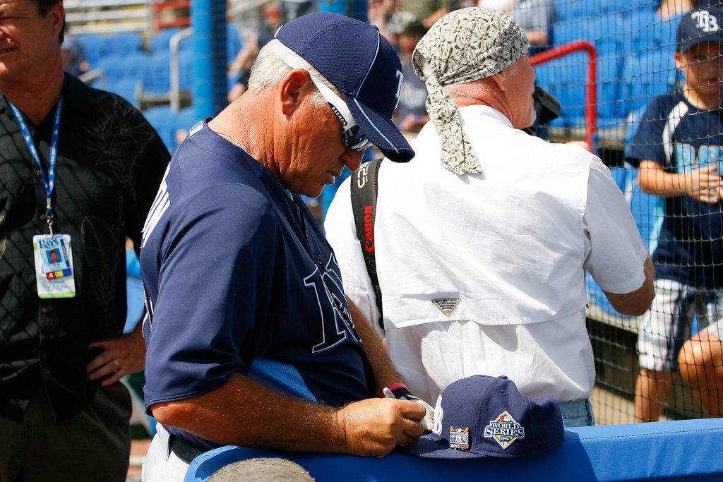 Tampa Bay Rays manager Joe Maddon (70) signs autographs for fans prior to a Grapefruit League Spring Training Game at the Florida Auto Exchange Stadium.