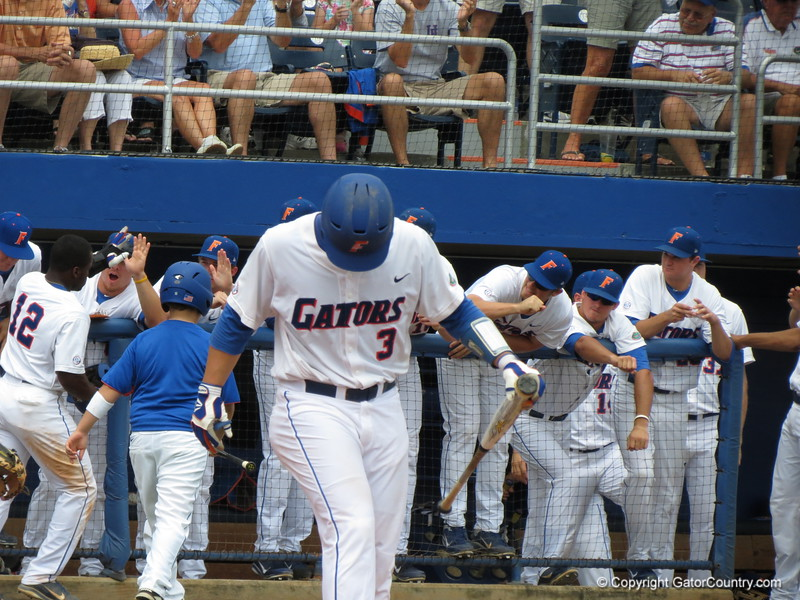 Players high-five Josh Tobias after he scored UF's first run as Mike Zunino digs in during the Gators' game against North Carolina State in Game 1 of the Gainesville Super Regional in McKethan Stadium on June 9, 2012.