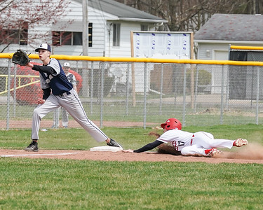 Lorain Tyrus Brewer awaits the throw as Elyria Hayden Lowstetter slides safely into third base Saturday April 13.  photo Joe Colon