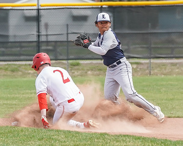 Lorain  Dominique Thompson tries to complete the double play after getting the force out on Elyria's Michael Knapp Saturday April 13.  photo Joe Colon