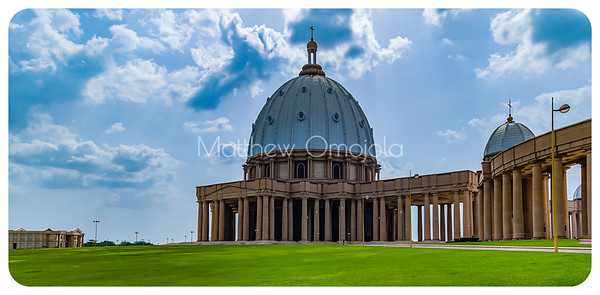 The major dome of the Basilica of Our Lady of Peace (Basilique Notre Dame de la Paix)  Yamoussoukro Ivory Coast Cote d'Ivoire. A minor dome on the colonnade is on the right. The columns as seen from the East approach. On the far left is one of the two residencies behind the Basilica. This one is the Papal residence.