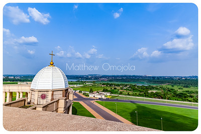 "Gardens around the Basilica of Our Lady Of Peace Yamoussoukro Cote d""ivoire, Ivory Coast West Africa. Remnant of coconut plantation, lake, and the city of Yamoussoukro in the distance.  West entrance and minor dome"