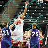 Bradley forward Raisa Taylor (34) drives for the basket early in the second half while Evansville forward Meagan Collins (21) and Samantha Heck (25) defend during the opening game of the MVC tournament. Bradley won the game 64-47.