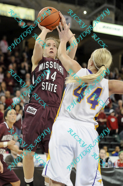 During the 2011 MVC tournament championship game Missouri State Karly Buer (14) puts up a shot for the first two points of the game while being defended by Northern Iowa Erin Brocka (44)  At halftime  Iowa was leading Missouri 35-15.