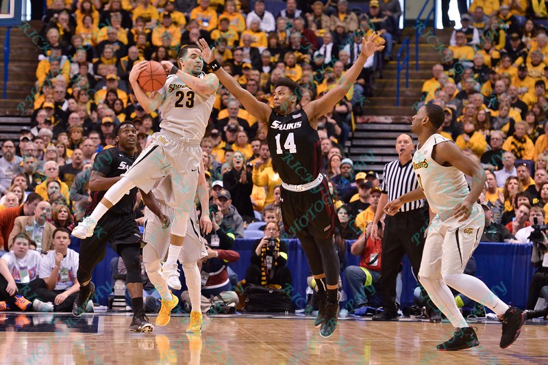Southern Illinois Salukis forward BOLA OLANIVAN (23) and Wichita State Shockers guard JOHN ROBERT SIMON (14) battle for a loose ball at the Missouri Valley Conference, Arch Madness Tournament game three where Wichita State defeated Southern Illinois by the score of 56-45