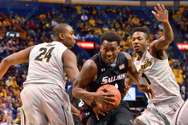 Southern Illinois Salukis guard JALEN PENDLETON (1) goes between the defense of Wichita State Shockers forward SHAQUILLE MORRIS (24) and Wichita State Shockers forward ZACH BROWN (1) on his way to the basket at the Missouri Valley Conference, Arch Madness Tournament game three where Wichita State defeated Southern Illinois by the score of 56-45