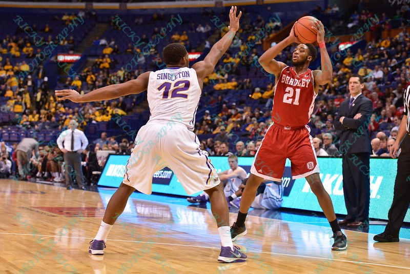 Bradley Braves forward JOSH CUNNINGHAM (21) looks to make a play against the defense of University of Northern Iowa Panthers forward MARVIN SINGLETON (12) at the Missouri Valley Conference, Arch Madness Tournament game five where U. of Northern Iowa defeated Bradley by the score of 71-46