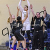Senior guard from Our Lady of Good Counsel, Lindsey Pulliam, jumps to pass the ball while surronded bu St Paul VI players and their coach offering encouragement to keep their arms up.