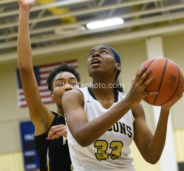 Rayne Tucker of OLGC puts one up with St Paulk's Mikayla Vaughn closing in from behind.