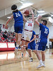 Riverdale's Logan Frey (24, left) swats the ball away from Arlington's Jason Launder (20) as he goes up for a layup.