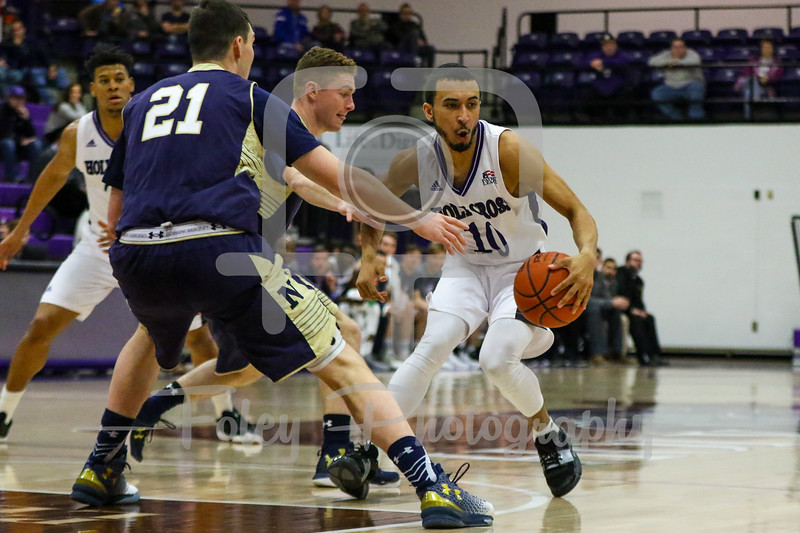 Holy Cross Crusaders guard Patrick Benzan (10) Navy Midshipmen forward George Kiernan (21)