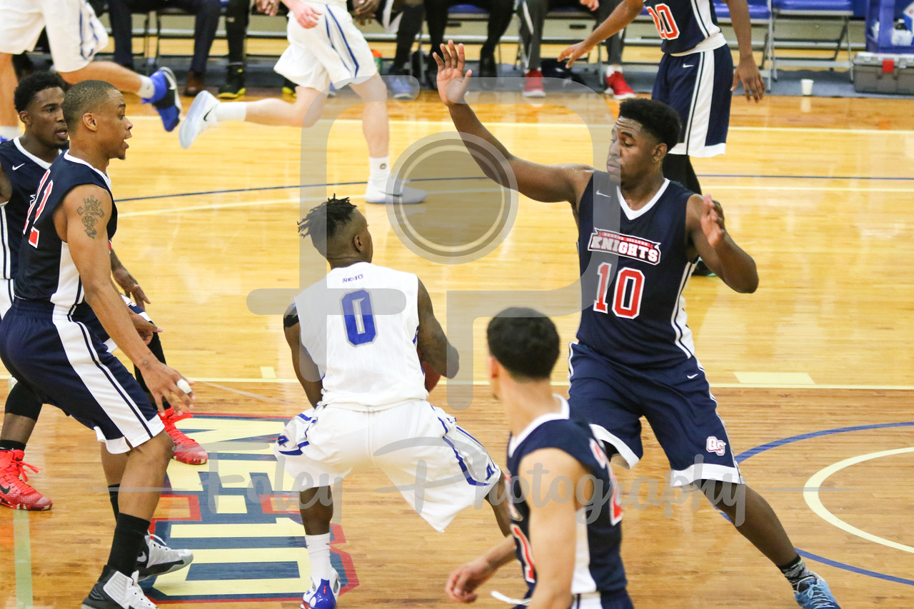 Assumption College guard Marcus Murray (0) Queens College Issac Grant (10)
