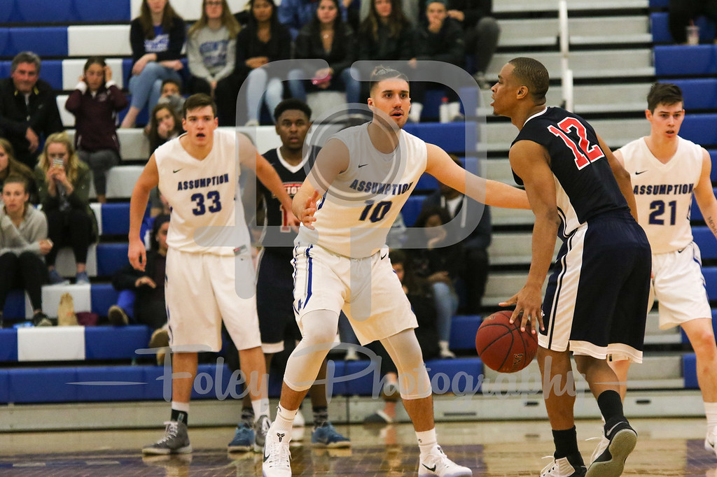 Assumption College forward Damien Rance (10) Queens College Tyree White (12)