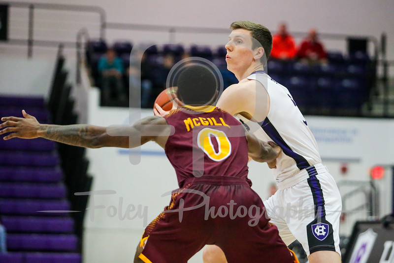 Holy Cross Crusaders forward Connor Niego (5) Iona Gaels guard Rickey McGill (0)