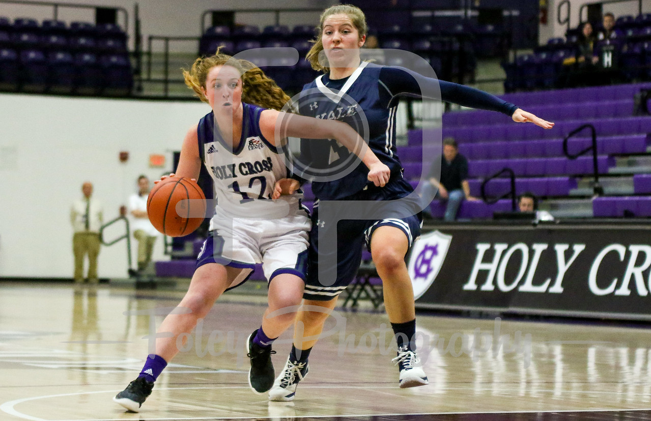 Holy Cross Crusaders guard Madalyn Smith (12) Yale Bulldogs guard Lena Munzer (24)