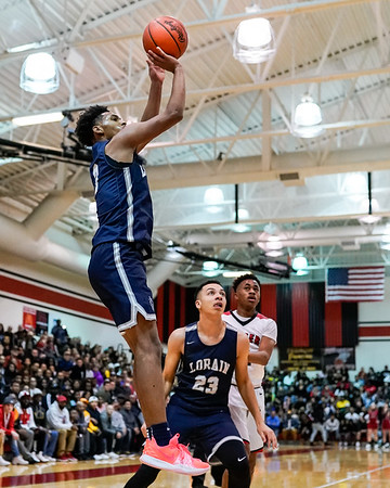 Lorain teamate #23 Aiden Brown watches as #3 Devon Grant takes the uncontested shot against Elyria Friday December 28.  Photo Joe Colon