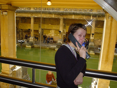 Guided Tour  Claire listening to the electronic guide with the main bath in the background.