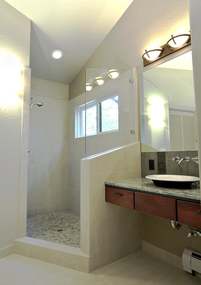 Floating vanity with vessel sink.  Open shower design with pebble floor.