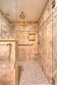 Wadatz Remodel After Rain head and handheld shower with controls mounted on the half wall.  Travertine stone goes to the ceiling.