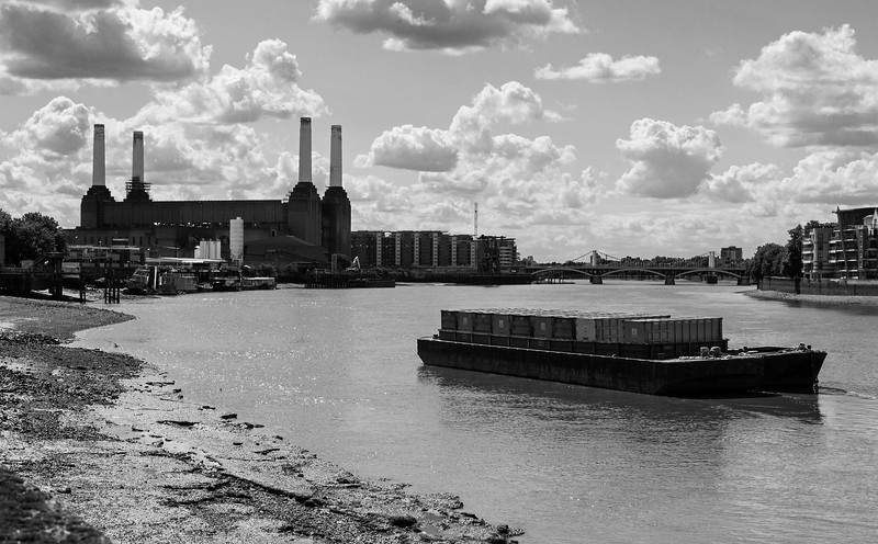 Barge on the River Thames at low tide and Battersea Power Station from Vauxhall Bridge in London, England