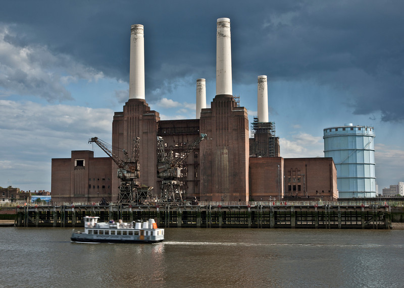 Colour image of a boat on the River Thames going past the iconic Battersea Power Station building