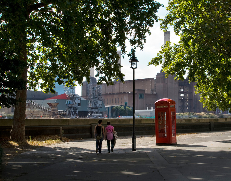 Colour image of walkers on the Chelsea Embankment in front of Battersea Power Station in London