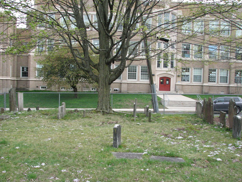 The grave is in the center foreground in this photo. If you enter from the main gate on Maple Av you will find the grave located about halfway front to back, and about 25 feet from the right hand edge of the cemetery.  Note the Fox School building in the background, and use it to help locate the grave. When I visited in 2019, the gate was locked, but a fallen section of fencing to the left of the gate allowed access.
