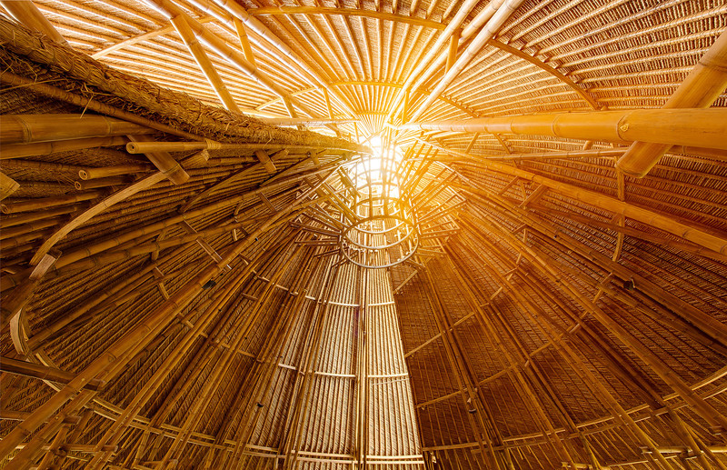"The interior of the Mandala Agung tower reveals bamboo arced into a graceful double spiral. The realization of  ""sacred geometry"" was a guiding principal in the construction Fivelements Healing Center. The open architecture admits soft natural light and a cooling breeze."