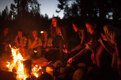 Campers roasting marshmallows around a campfire